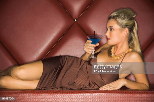 Woman in evening dress drinking cocktail