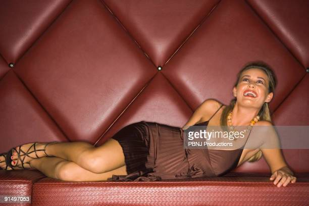 Woman in evening dress laying in cushioned booth