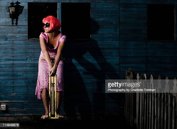 Woman in evening dress on pogo stick by shed