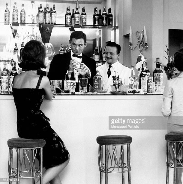 A woman in evening dress ordering a drink sitting on a stool at the bar 1960s