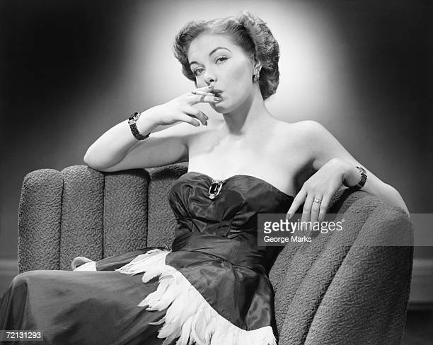 Woman in evening dress smoking cigarette (B&W), portrait