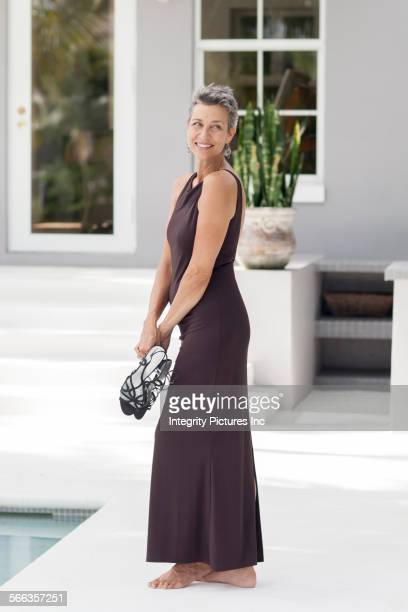 woman in evening gown carrying shoes by swimming pool - grey dress stock pictures, royalty-free photos & images