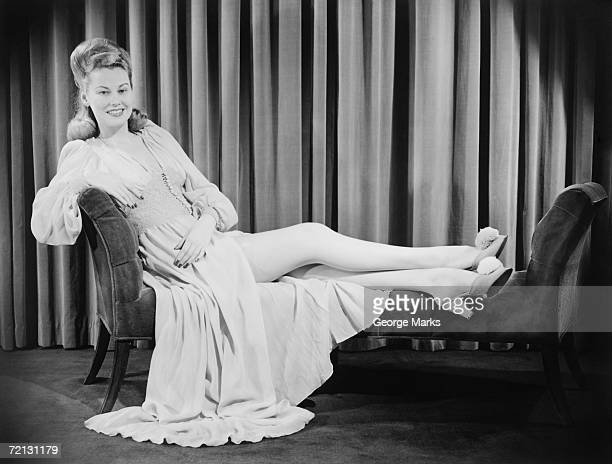 Woman in evening gown reclining on chaise longue (B&W), portrait