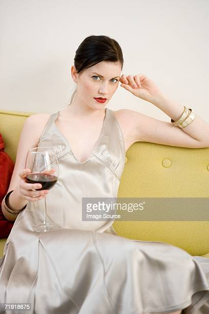 woman in evening gown sitting on sofa - beautiful women breast stock pictures, royalty-free photos & images