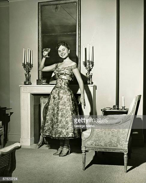 Woman in evening gown toasting by fireplace, (B&W), portrait