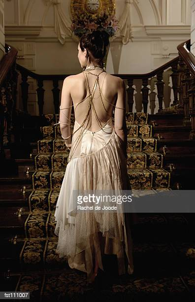 woman in evening gown walking up stairs - evening gown stock pictures, royalty-free photos & images