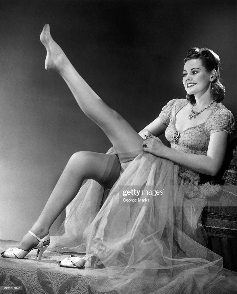 Woman in evening wear pullin on silk stockings : Stock Photo