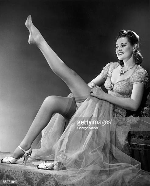 woman in evening wear pullin on silk stockings - bas nylon photos et images de collection