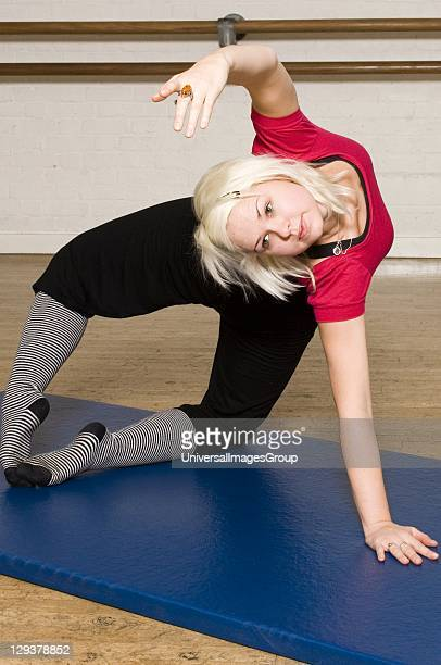 Woman in exercise class practicing Pilates advanced mermaid posture An exercise class at the Body Control Centre in London perform a Pilates Advanced...