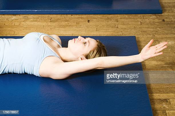 Woman in exercise class practicing Pilates backward swimming routine An exercise class at the Body Control Centre in London in a Pilates Backward...