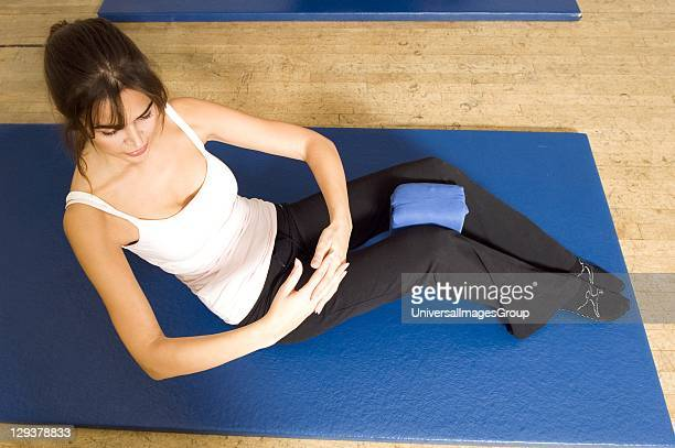 Woman in exercise class practicing Pilates oblique twist curl back position An exercise class at the Body Control Centre in London practice a Pilates...