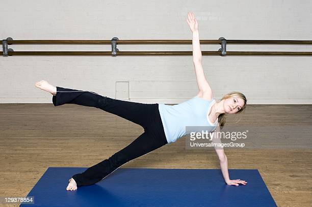 Woman in exercise class practicing Pilates star position An exercise class at the Body Control Centre in London in the Pilates Star position Pilates...