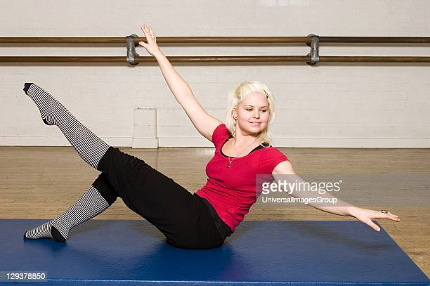 Woman in exercise class practicing Pilates teaser preparation An exercise class at the Body Control Centre in London prepare for a Pilates Teaser...