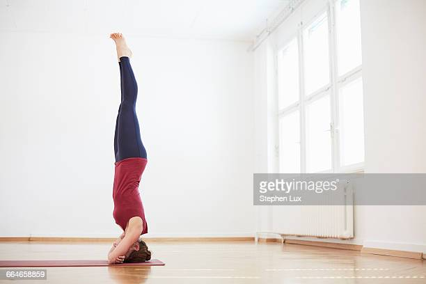 Woman in exercise studio doing headstand