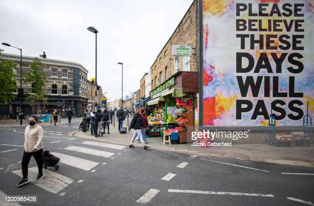 Woman in face mask walks past a poster stating 'Please beleive these days will pass' in East London on April 25, 2020 in London, England. The British...