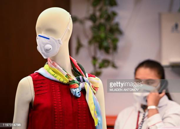 Woman in face masks talks on the phone beside a mannequin wearing a mask at a shopping mall in Bangkok on January 29, 2020. - Thailand has detected...