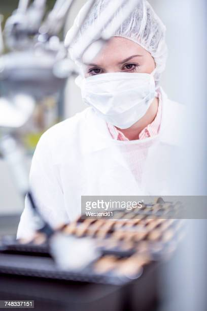 Woman in factory looking at robot handling cookies