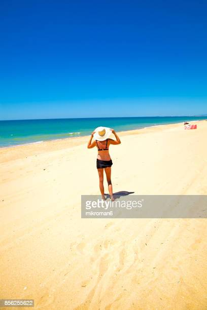 a woman in faro beach on very hot summer day. faro, portugal - faro city portugal stock photos and pictures