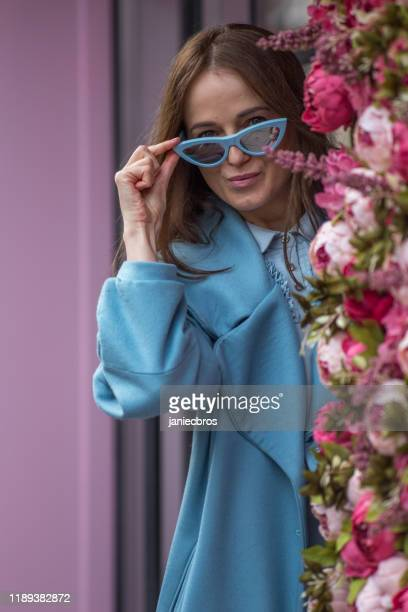 woman in fashion outfit posing on spring flower wall - fashion week stock pictures, royalty-free photos & images