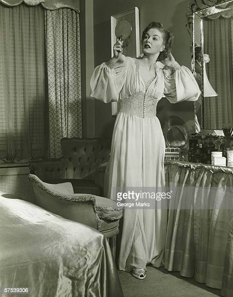 woman in fashionable gown looking at mirror in bedroom, (b&w) - women in slips stock photos and pictures