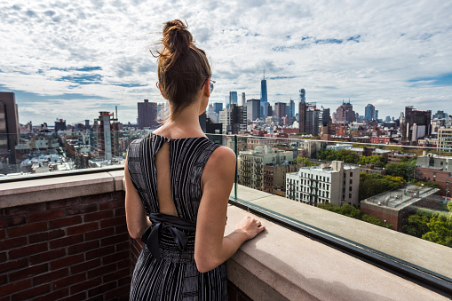Woman in fashionable jump suite looking at Manhattan view from East Village rooftop - gettyimageskorea