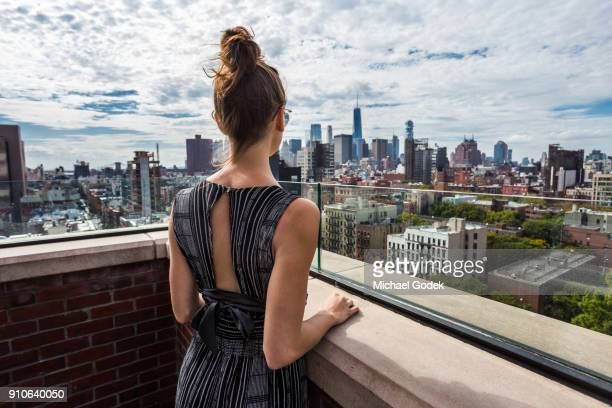 woman in fashionable jump suite looking at manhattan view from east village rooftop - street style new york stock pictures, royalty-free photos & images