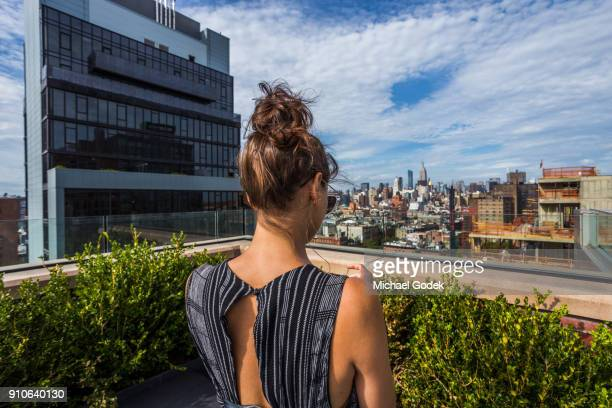 Woman in fashionable jump suite looking at Manhattan view from East Village rooftop