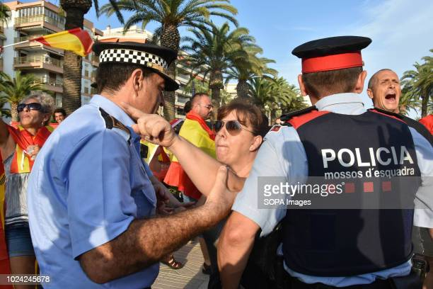 A woman in favor of the unity of Spain seen confronting with Proindependence protesters in front of the police during the demonstration