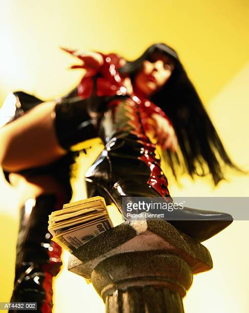 woman in fetish wear stepping on pile of money, low angle view - dominatrice photos et images de collection