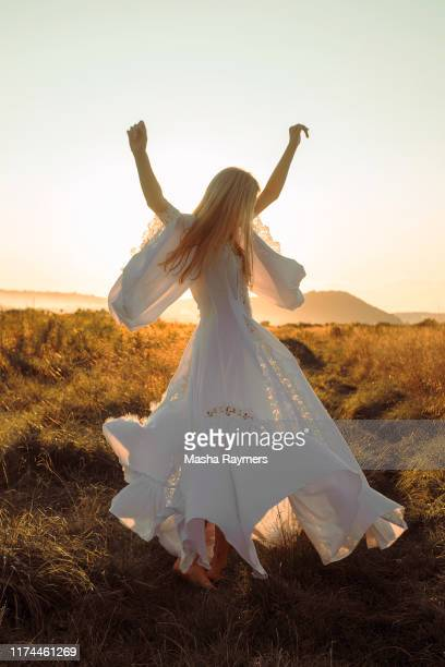 woman in field in beautiful white dress sunny weather - white dress stock pictures, royalty-free photos & images