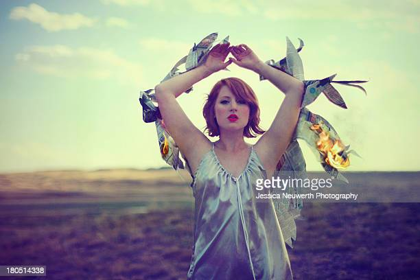 Woman in field with fiery newspaper wings