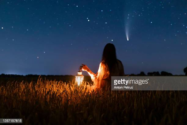 woman in field with lantern on background of comet neowise c/2020 f3 - astronomie stockfoto's en -beelden
