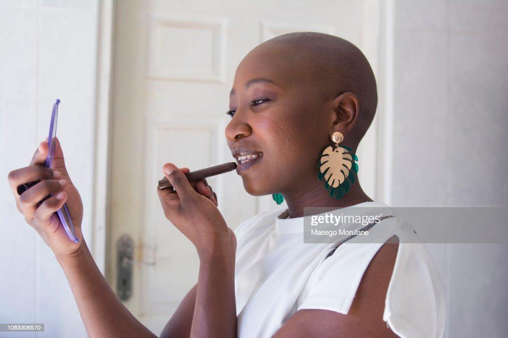 Woman putting on lipstick : Stock Photo