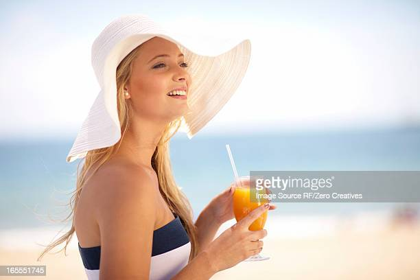 Woman in floppy hat having juice