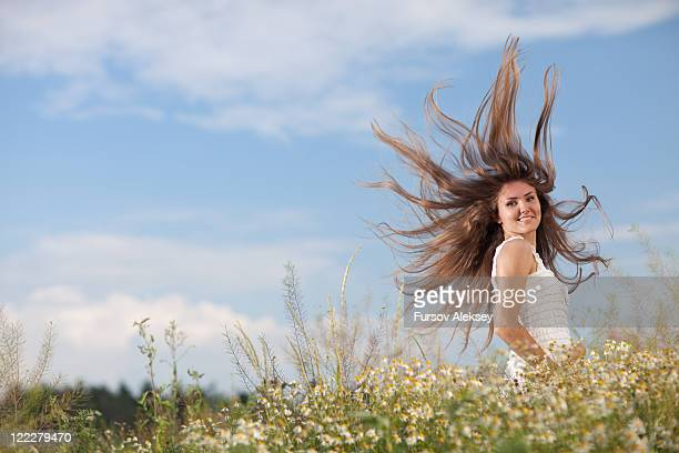 Woman in flower field with hair blowing