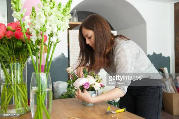 Woman in flower shop arranging bouquet