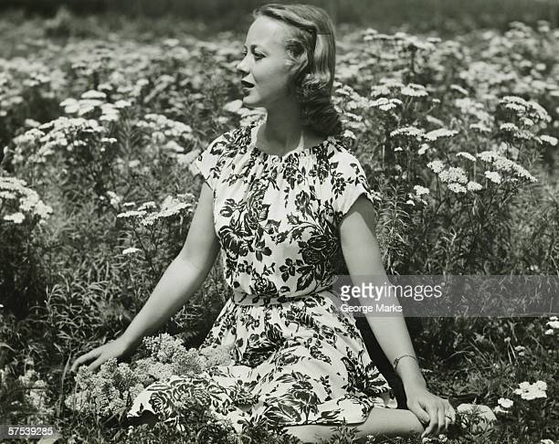 Woman in flowery dress sitting in meadow among flowers, (B&W), portrait