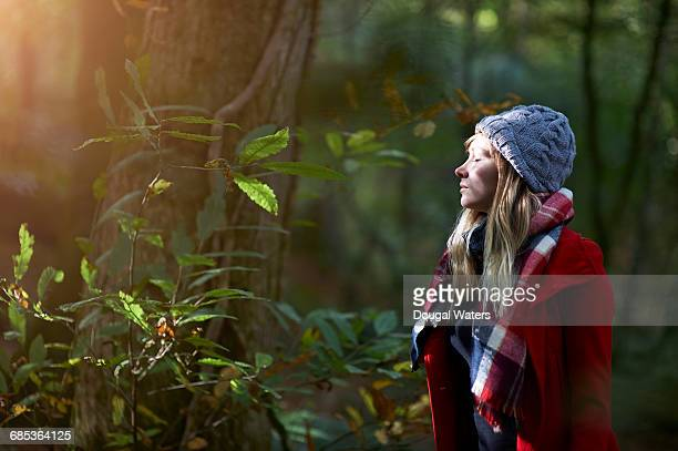 Woman in forest with sunlit face and closed eyes.