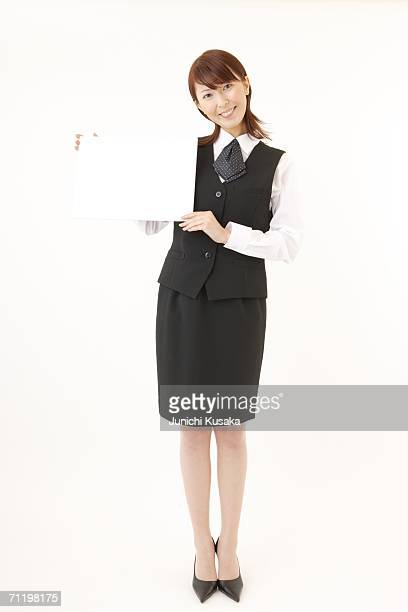 a  woman in formal attire holding a blank message - ベスト ストックフォトと画像