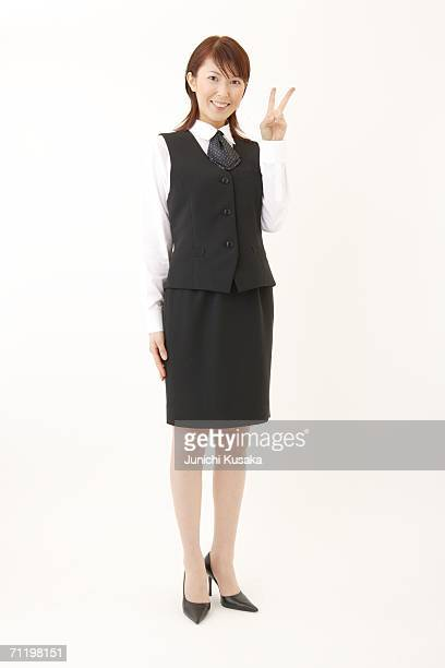 A  woman in formal attire smiling with peace sign
