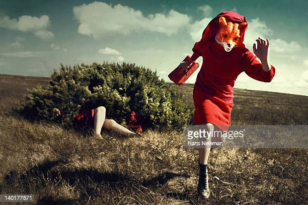 Woman in fox costume running with a briefcase with a woman lying in bush behind her