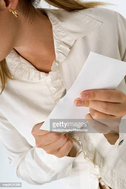 Woman in frilly blouse opening a letter with a letter opener, close-up