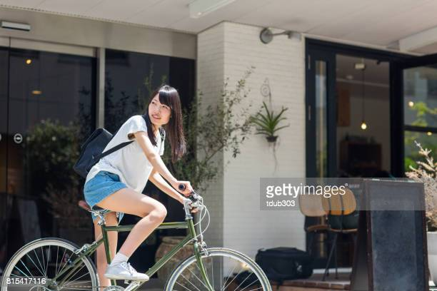 Woman in front of a hotel with a rental bicycle