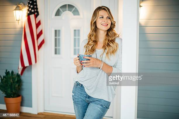 Woman in front of a house.