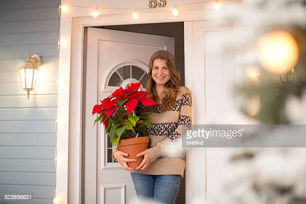 mujer frente a una casa. - flor de pascua fotografías e imágenes de stock