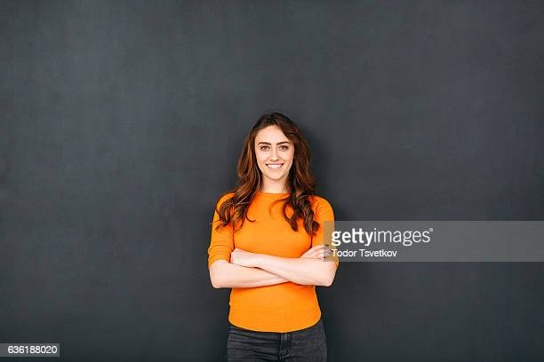 woman in front of blackboard - oranje stockfoto's en -beelden