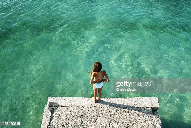 Woman in front of blue water