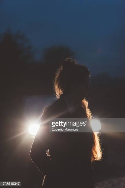 Woman in front of car headlights on roadside at night