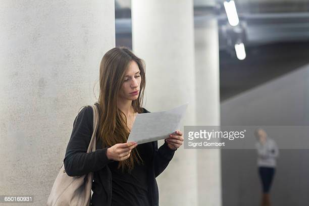woman in front of columns looking at paperwork - sigrid gombert stock pictures, royalty-free photos & images