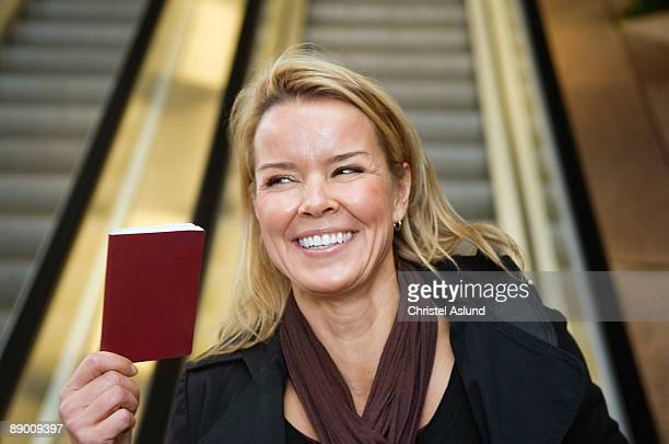 Woman in front of escalator holding passport